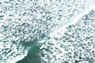 Aerial view of a surfer in the middle of the pattern create by the foam of a wave. Piha black sand beach New Zealand