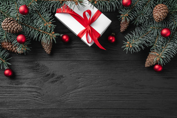 Christmas card with white gifts and fir branches on a dark wooden rustic background, place for text. Xmas and happy new year greeting card. Top view, flat lay.