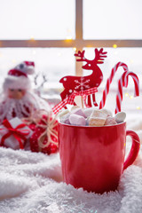 Christmas decor: a warm blanket, a cup of hot cocoa with marshmallow gifts, candles and a Christmas tree on the windowsill by the window. Winter mood, festive decoration.