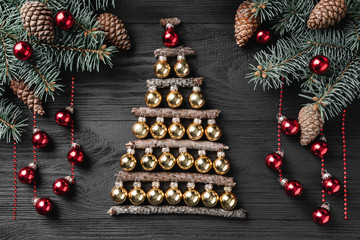 Christmas tree made of christmas balls  on a dark wooden background. Xmas and happy new year greeting card. Top view, flat lay