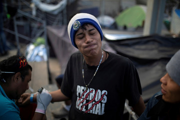 Marcos from El Salvador, part of a caravan of thousands of migrants from Central America trying to reach the United States, reacts while getting a tattoo of the name of his wife Maria Jose at a temporary shelter in Tijuana