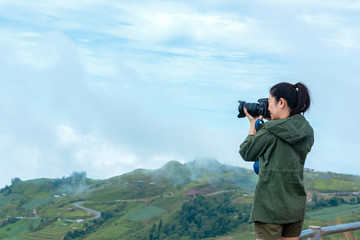 Professional lifestyle woman photographer taking with prime lens outdoor in the mountain, winter season.  Travel Concept