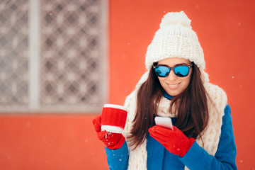 Winter Girl With Hot Beverage Checking Her Smartphone