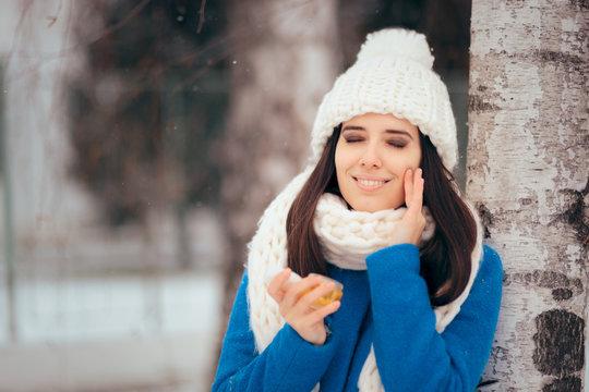 Happy Woman Applying Skin Moisturizing Cream Outdoors in Winter