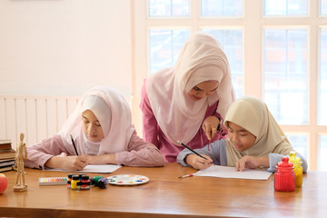 Adult muslim female teaching with art to learning a two child girl in home, islam education concept.