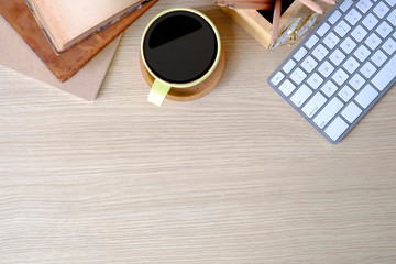 Office desk top view computer, coffee and books on wood table.