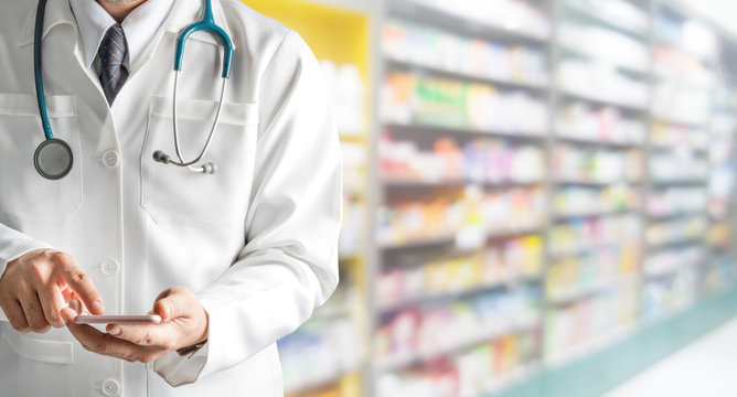 Male pharmacist using mobile phone at pharmacy. Medical healthcare and pharmaceutical service.