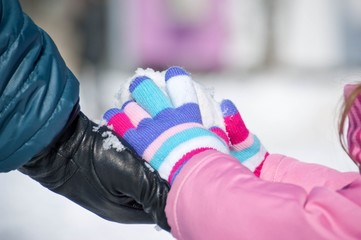 Baby toddler hands with colorful textile gloves playing with snow. Snow on the ground. Shallow depth of focus. Natural texture background. Winter concept, family games outdoor.
