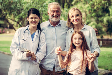 Happy healthy family and doctor talking in the park. People healthcare and medical staff service concept.