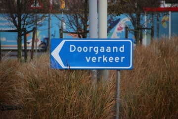 Blue direction sign in the netherlands for ongoing traffic in the harbor of Rotterdam .