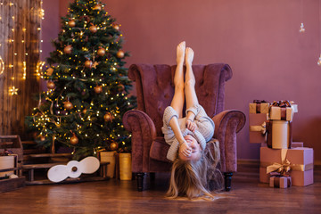 Beautiful young woman dressed in a sweater laying in the arm chair up side down next to the christmas tree.