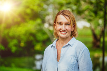 Portrait of happy middle aged woman standing in the park. The woman is smiling with happiness.
