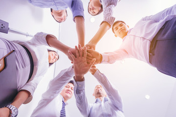 Group of business people join hands in office. low angle view