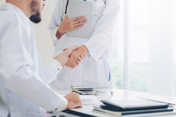 Doctor at the hospital giving handshake to another doctor showing success and teamwork of professional healthcare staff.