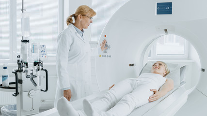 In Medical Laboratory Radiologist Controls MRI or CT or PET Scan with Female Patient Undergoing Procedure. High-Tech Modern Medical Equipment. Friendly Doctor Chats with Patient. Wall mural