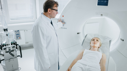 In Medical Laboratory Male Radiologist Controls MRI or CT or PET Scan with Female Patient Undergoing Procedure. High-Tech Modern Medical Equipment.