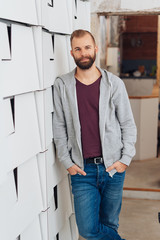 Casual man leaning on wall and smiling at camera