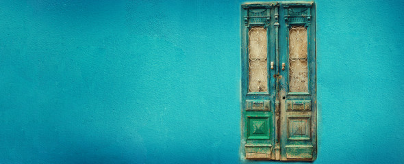Old turquoise wooden door on blue wall with copy space. Texture background. Pop art concept, vintage style