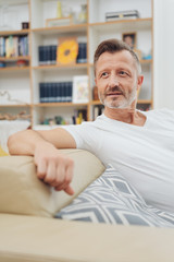 Man relaxing on a sofa watching something behind