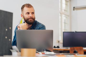 Happy entrepreneurial man in office work space