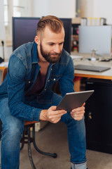 Stylish, modern man looking at tablet in office