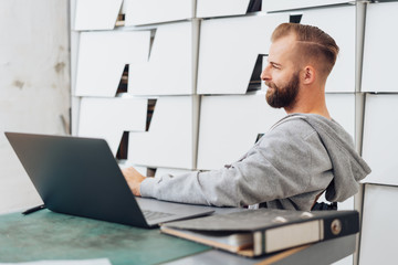 Young, casual man in contemplation at office desk