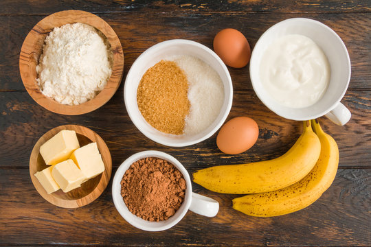 Ingredients for chocolate banana bread - flour, cocoa, sugar, eggs, butter, sour cream, baking powder on the wooden rustic table, top view.