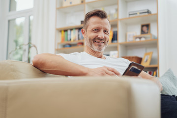 Smiling friendly older man relaxing on a sofa
