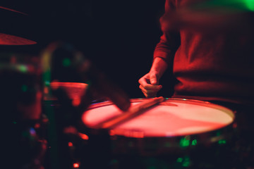 Human hands playing the drum with drumstick.