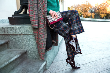Close up fashion woman sitting in high heel shoes hold black trendy handbag . Stylish outfit checkered pants and coat.Street fashion details of elegant outfit,ankle sock boots, holding leather handbag Wall mural