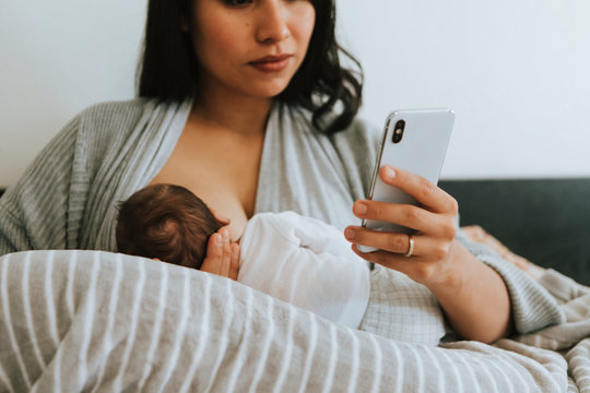 Breastfeeding mother using a smartphone