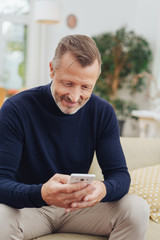 Man smiling to himself as he reads a text message