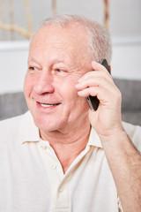 Senior mit Smartphone hört aufmerksam zu
