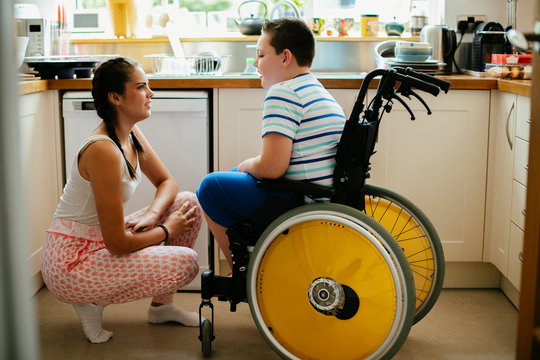 Sister helping her disabled brother in the kitchen
