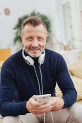 Middle-aged man listening to music on headphones