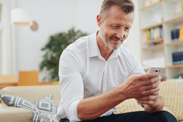 Middle-aged man smiling as he reads an sms