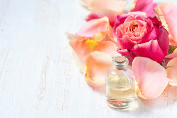 Bottle with essential aroma oil on white wooden background.