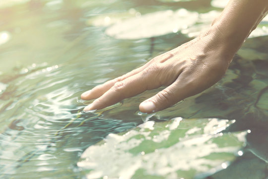 person touches the water with his hand