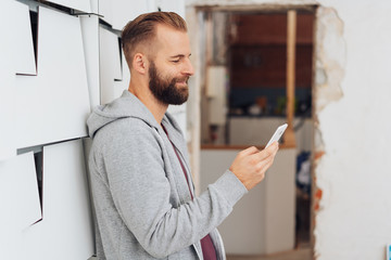 Casual man at home smiling while texting on phone