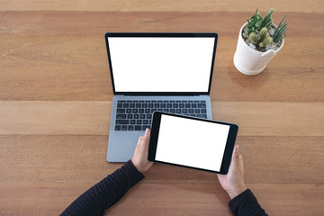 Top view mockup image of hands holding a black tablet and laptop with blank white screen on wooden table in office