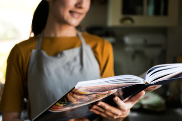 Japanese woman reading a cookbook in the kitchen
