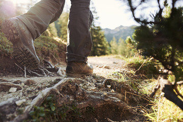Wanderschuhe beim Laufen als Detail in Bewegung mit Fels und Steinen