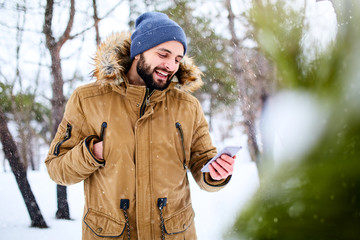 Smiling bearded man wears warm winter clothes and using smartphone with fast internet data connection in country side. Handsome man texting with cellphone and using apps in forest. Snowfall in woods.