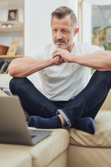 Middle-aged man sitting cross legged on a sofa