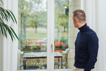 Man standing indoors staring out of the window