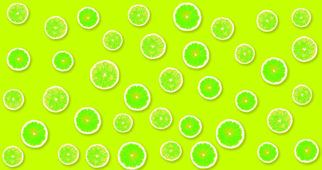 Background with green, fresh lemons on a lime color background