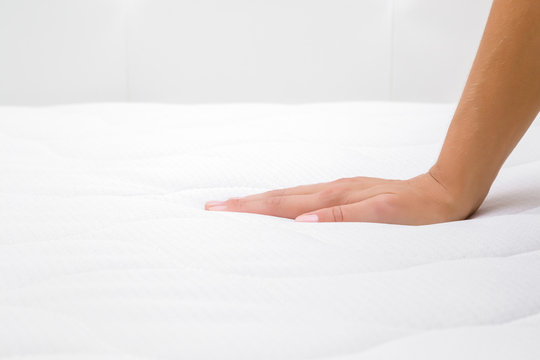 Woman's hand pressing on white mattress. Checking hardness and softness. Choice of the best type and quality. Side view. Close up.
