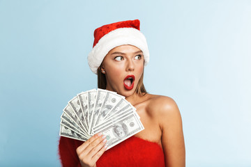 Happy young woman wearing christmas hat posing isolated over blue wall background holding money.