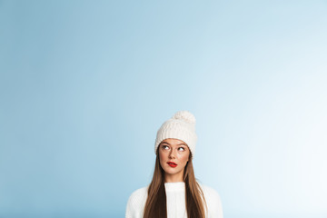 Thinking young woman wearing winter hat posing isolated over blue wall background.