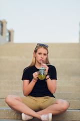 Pretty blonde girl with glass refreshing lemonade